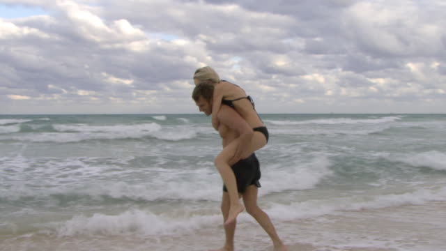 ws couple playing in ocean waves / miami, florida, usa - piggyback stock videos & royalty-free footage