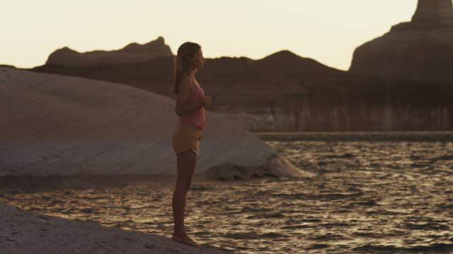 WS PAN Couple playing near Lake Powell at sunset / Utah, USA