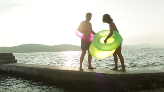 couple playing on jetty with inflatable rings. - ブラック島点の映像素材/bロール