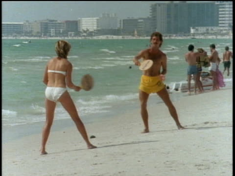 couple playing paddleball on florida beach - 1985年点の映像素材/bロール