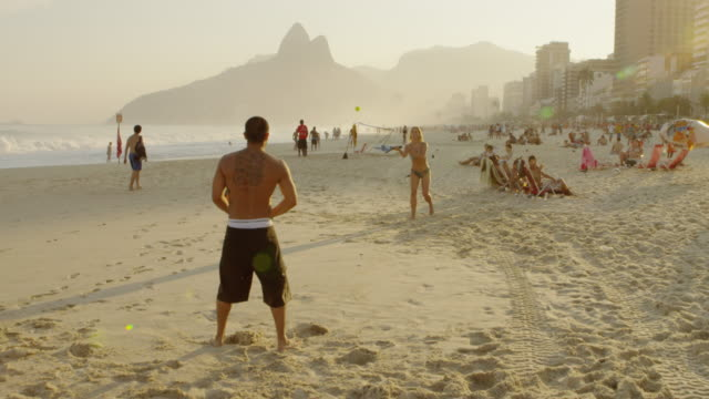 vídeos de stock e filmes b-roll de a couple playing tennis on ipanema beach together - raqueta