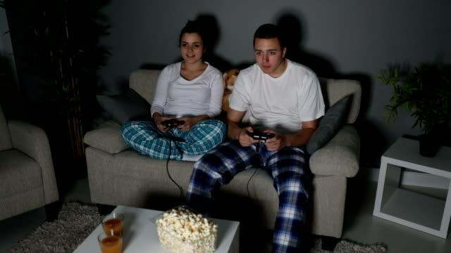 vídeos y material grabado en eventos de stock de pareja jugando videojuegos en la sala de estar - juego electrónico de bolsillo