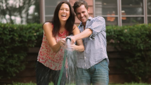 Couple playing with hose in backyard