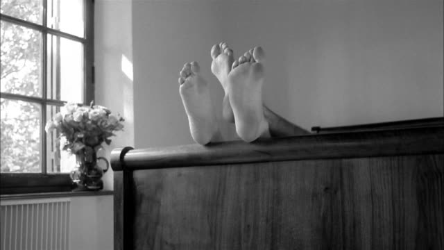 A couple plays footsie on top of the footboard of a bed.