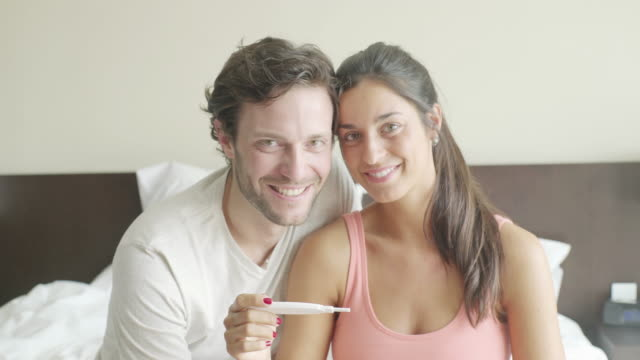couple pleased with pregnancy test results - pregnant stock-videos und b-roll-filmmaterial