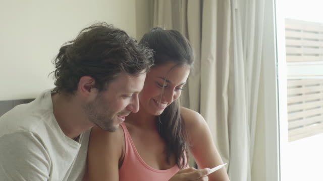 couple pleased with pregnancy test results - vest stock videos & royalty-free footage