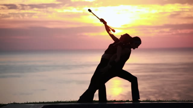 vidéos et rushes de ms couple poi dancers silhouette performing with firesticks in front of sunrise and ocean / montezuma, costa rica - kelly mason videos