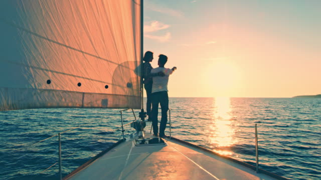 vídeos de stock e filmes b-roll de ws couple pointing at the horizon from a sailboat at sunset - vela desporto aquático
