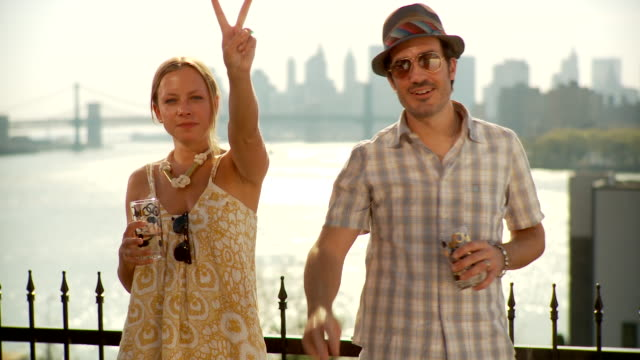 MS Couple posing in front of sea, showing hand signs / Brooklyn, New York