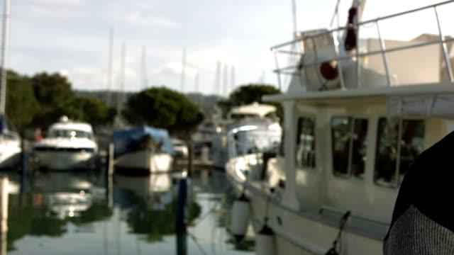hd: couple posing in front of their boat - förtöjd bildbanksvideor och videomaterial från bakom kulisserna