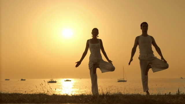 HD: Couple Practicing Yoga At Sunset