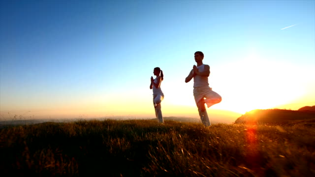 couple practicing yoga at sunset - buddhism stock videos & royalty-free footage