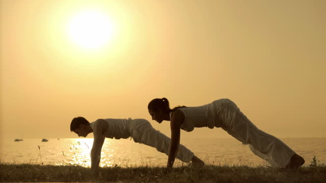 HD: Couple Practicing Yoga On The Beach