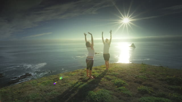 MS POV TS SLO MO Couple practicing yoga overlooking Pacific Ocean / Port Orford, Oregon, United States