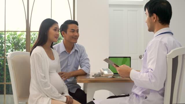 カップルの妊娠中の女性を参照してください医師 - 人間の消化器官点の映像素材/bロール