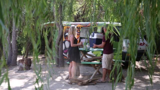 vídeos y material grabado en eventos de stock de a couple prepares a campsite. - nevera portátil