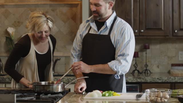 ms tu couple preparing food in kitchen / orem, utah, usa - orem video stock e b–roll