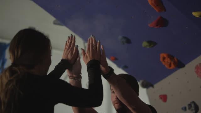 couple psyching each other up while man climbs rock wall at gym - friklättring bildbanksvideor och videomaterial från bakom kulisserna
