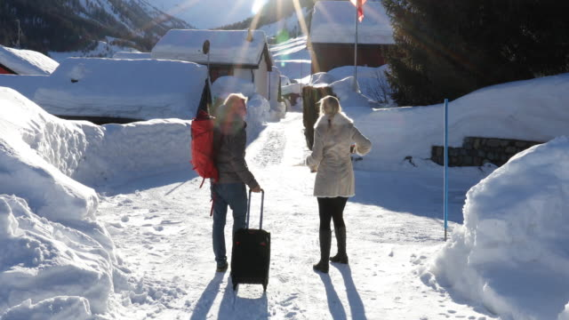 couple pull/carry travel bags after snow, in swiss village - mature couple stock videos & royalty-free footage