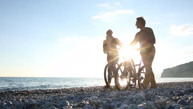 Couple push bicycles along beach, looking out to sea