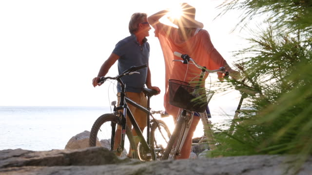 couple push bikes between coastal rocks, look out to sea - maglietta polo video stock e b–roll
