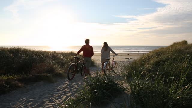 couple push bikes thru sand dunes and grass to beach, sunset - oregon coast stock videos & royalty-free footage