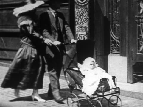 b/w 1906 couple pushing baby in carriage on sidewalk / man stops, enters bar + exits quickly / nyc - carriage stock videos & royalty-free footage