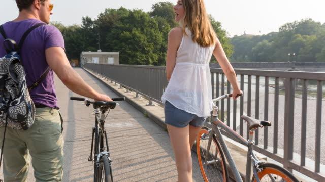 Couple pushing bicycles along river