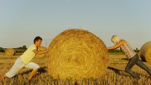 HD: Couple Pushing Hay Bale Against Each Other
