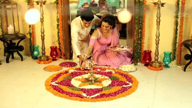 MS PAN Couple putting diyas on flower rangoli during diwali festival