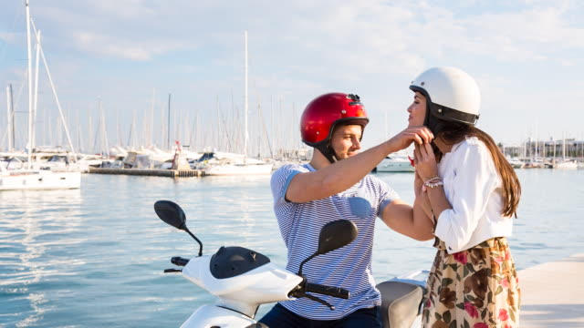 MS couple putting on helmets to ride scooter at yacht harbor