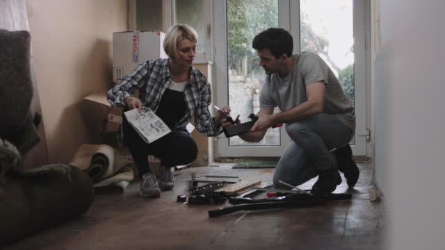 couple putting together flatpack shelving - wohnraum stock-videos und b-roll-filmmaterial