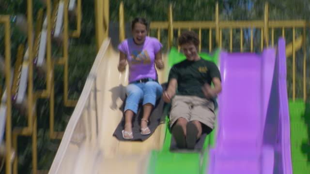 couple racing down slide - anno 2004 video stock e b–roll