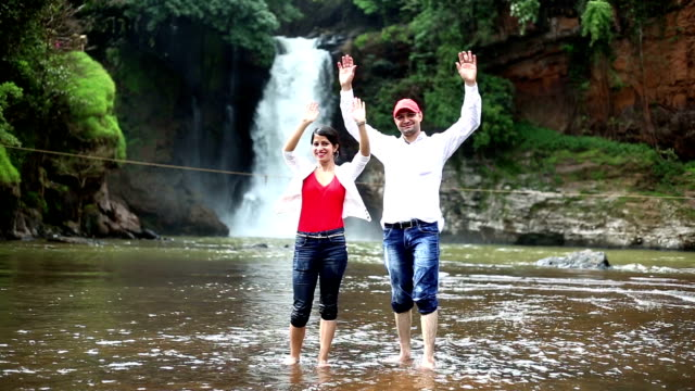 Couple, levant les mains vers le haut dans l'air en face de la cascade