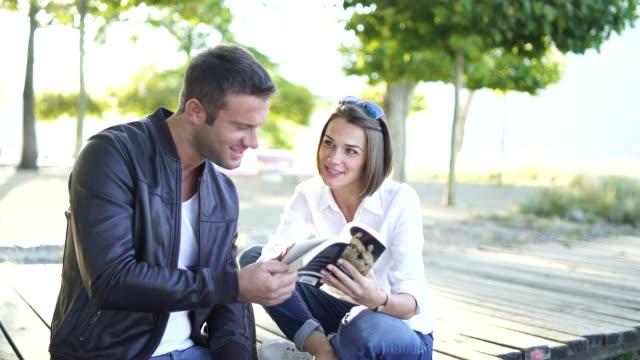 vídeos y material grabado en eventos de stock de par leer un libro a lo largo de un lago en un día soleado - camisa con botones