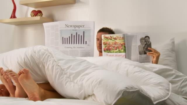 vídeos de stock e filmes b-roll de carrinho de hd: casal na cama a ler - casado