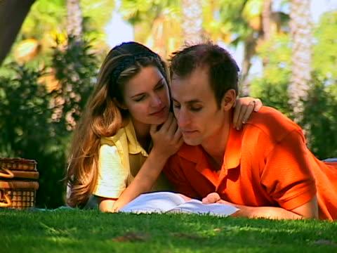 vídeos de stock e filmes b-roll de couple reading in the park - encostado