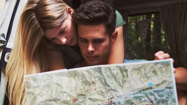 couple reading map in van during vacation - guidance stock videos & royalty-free footage