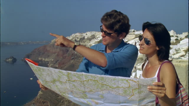 ms couple reading map with hilltop village in background / oia, santorini, greece - oia santorini stock videos & royalty-free footage