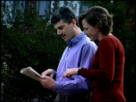 stockvideo's en b-roll-footage met couple reading newspaper outdoors - mid volwassen koppel