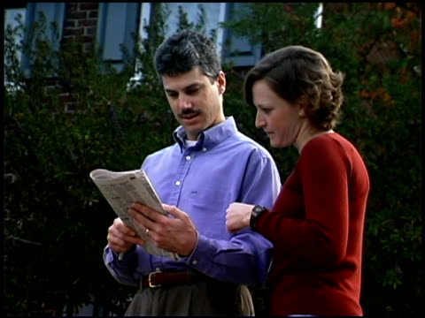 stockvideo's en b-roll-footage met couple reading newspaper - mid volwassen koppel