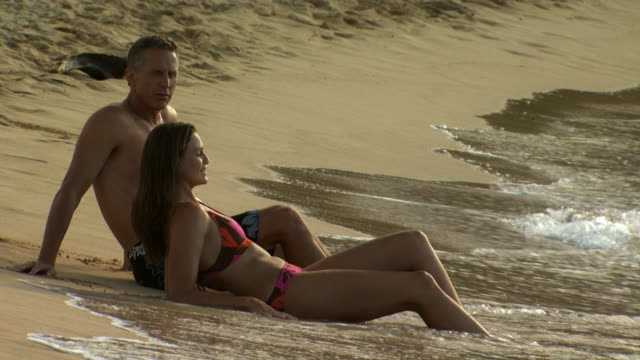 couple reclining on sandy beach - see other clips from this shoot 1142 stock videos & royalty-free footage