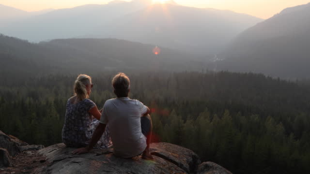 couple relax above forest and mountains at sunrise - mature couple stock videos & royalty-free footage