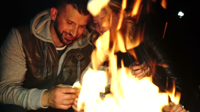 couple relax around campfire, roasting marshmallows - marshmallow video stock e b–roll