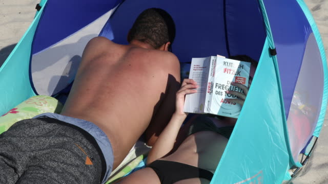 a couple relax at beach while the woman reads a book at high summer temperatures around 30 degrees celsius during the novel coronavirus crisis on... - swimming shorts stock videos & royalty-free footage