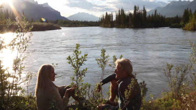 couple relax at edge of mountain river, looking off - pensionierung stock-videos und b-roll-filmmaterial