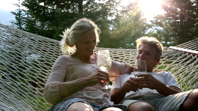 Couple relax in hammock with glasses