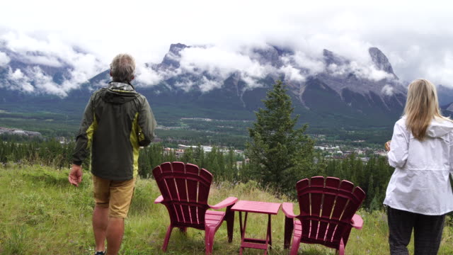 Couple relax in meadow chairs, look out across mountains