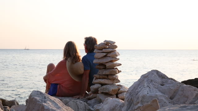couple relax next to stack of zen rocks, look out to sea - stack rock stock videos and b-roll footage