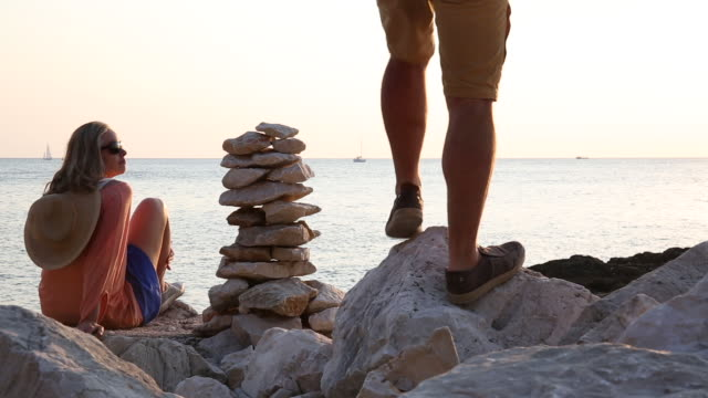 couple relax next to stack of zen rocks, look out to sea - next to stock videos and b-roll footage